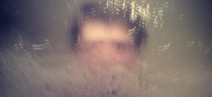 e kijkt door een beslagen spiegel